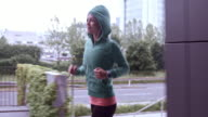 SLO MO TS Woman in a hoodie running along the city street video