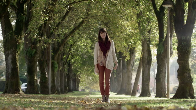 A woman in a park walks through a long row of trees, during the day video