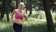 SLO MO DS Woman in a pink top running through the forest video