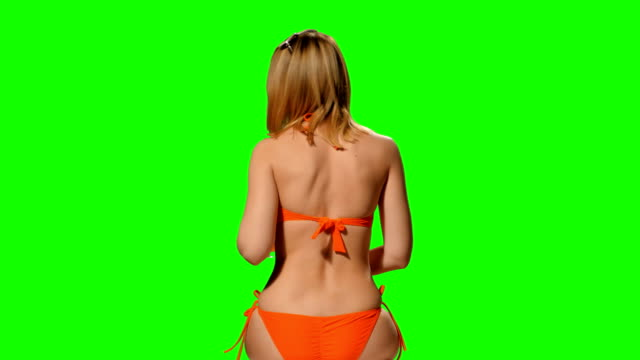 A woman in a swimsuit on a green background (alpha channel) video