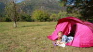Woman in a tent using digital tablet video
