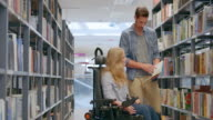 Woman in wheelchair browsing through book with friend in library video