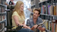 DS Woman in a wheelchair reading a book with a friend in the library video