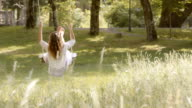 SLO MO Woman in white dress on swing in nature video