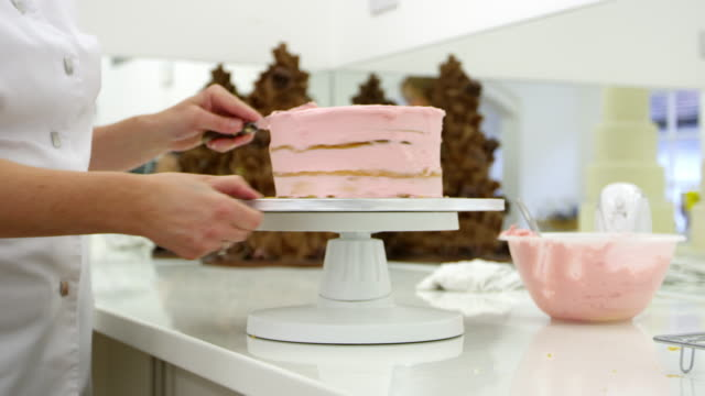 Woman In Bakery Decorating Cake With Icing video