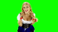 Woman in bavarian costume playing with her hair and laughs. Green screen video