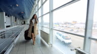 Woman in beige coat talks on phone and goes through airport video