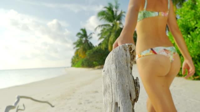 SLOW MOTION: Woman in bikini walking on white sand beach video