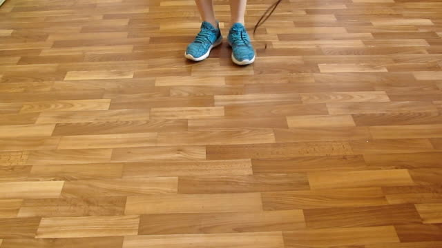 Woman in blue sneakers jumps rope on a wooden floor - 20sec video