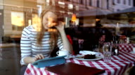 Woman in cafe using tablet PC and eating dessert video