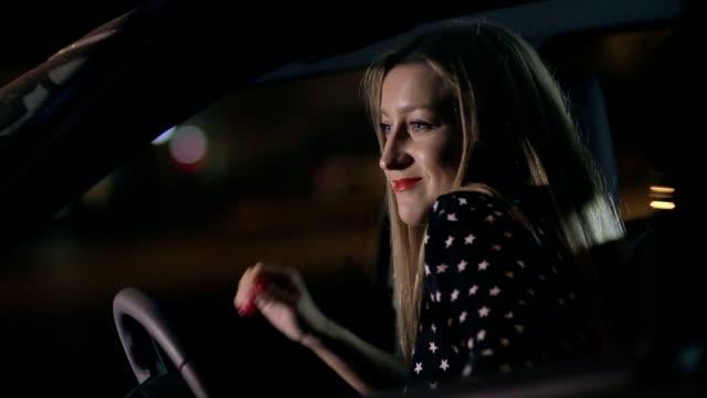 Woman in car having fun at night dancing video