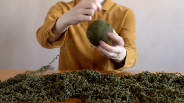 Woman in dress clewing yarn up video