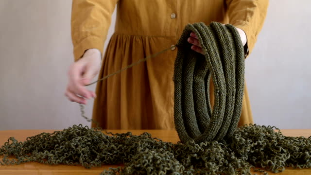 Woman in dress unravelling the woolen hat video