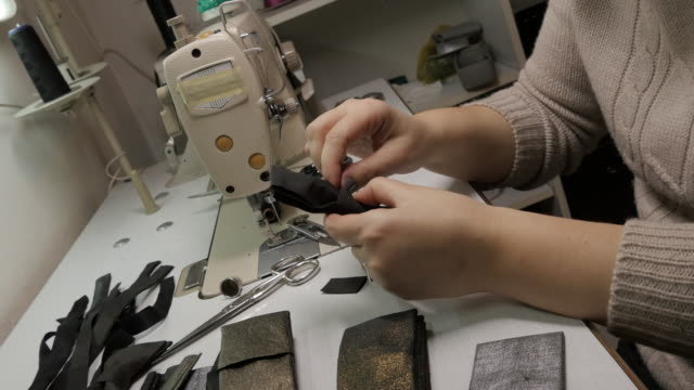 CU Woman in factory sewing bow tie video