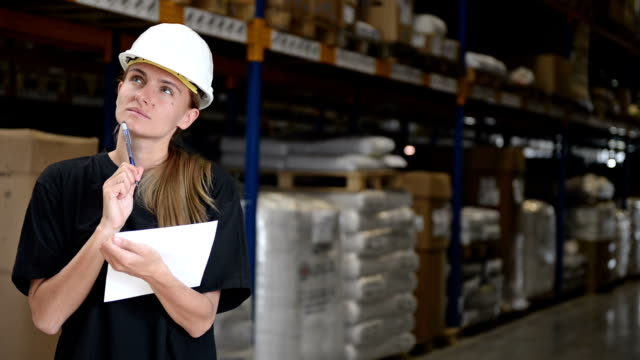 Woman in factory thinks, writes and smiles video