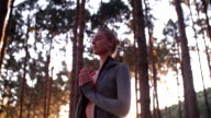 Woman in forest with her hands together doing breathing exercises video