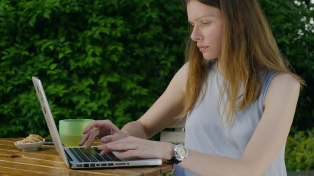 Woman in garden is typing on laptop. video