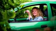 Woman in green car showing her car keys video
