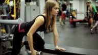 Woman in gym lifting dumbbell at bench video