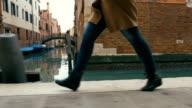 Woman in haste moving along Venetian canal video