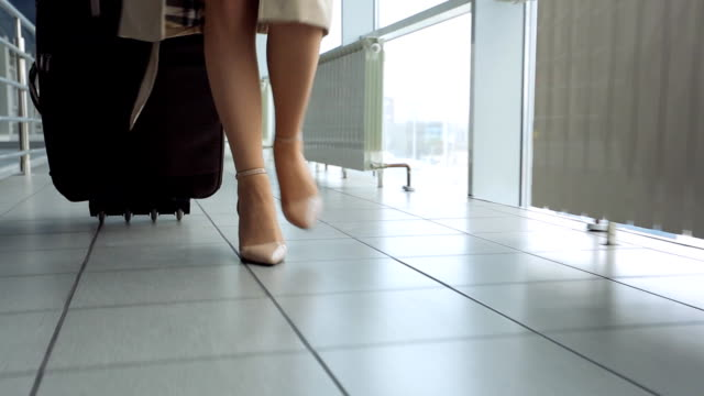 Woman in heels goes at airport and roll suitcase on wheels video