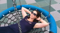 Woman in her thirties  (30s) daydreaming about life on a swing in the playground video