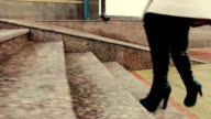 Woman in high heeled boots going up stone staircase video
