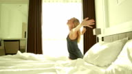 Woman in hotel room, arms outstretched video