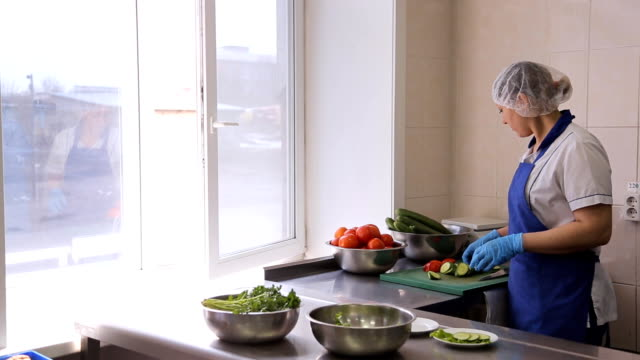 A woman in kitchen in an apron spread sliced tomatoes and cucumbers on a plate video