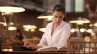 DS Woman in library using a tablet and a book video