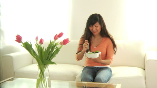 Woman in living room eating salad video