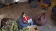 Woman in loft room with grunge urban interior using app on smartphone video