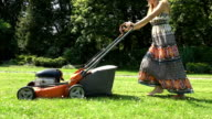 woman in long dress cut grass in own yard with lawn mower video
