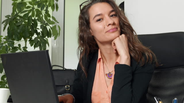 Woman in office in front of a laptop video