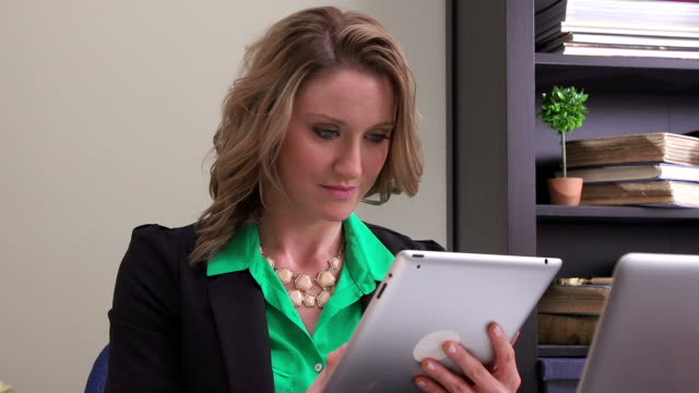 Woman in office looking at tablet video