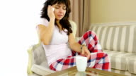 Woman in pajamas is talking on mobile phone at home, a cup of coffee on the table video