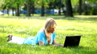 Woman in park using laptop. video