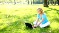 Woman in park working on laptop and smiling. video