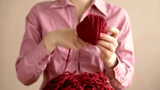 Woman in pink clewing the yarn up video