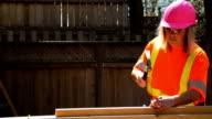 Woman in pink hardhat uses hammer video