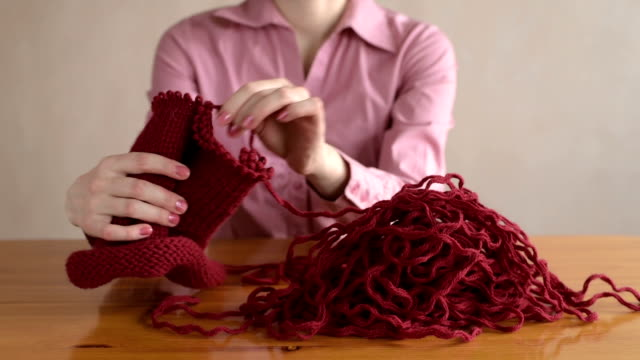 Woman in pink unravelling the knitting video