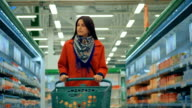 Woman in red coat pushing trolley in aisle at supermarket video