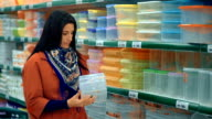 Woman in red coat shopping in supermarket video