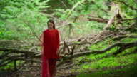 Woman in red dress in ancient forest video