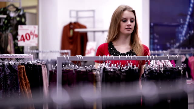 Woman in red dress shopping in clothing store video