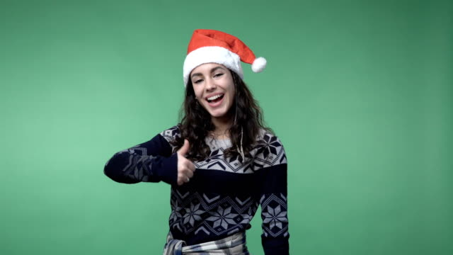 woman in santa's cap showing thumb up and smiling video
