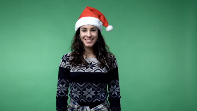 woman in santa's cap showing thumbs up and smiling video