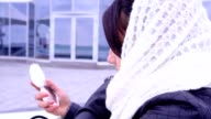 Woman in scarf looks in the mirror video