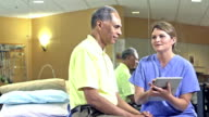Woman in scrubs with digital tablet talks to patient video