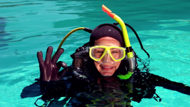 Woman in scuba diving doing ok sign video